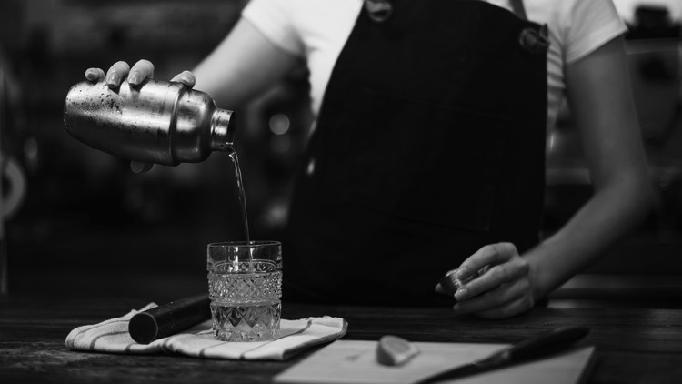 bartender straining cocktail